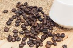 Kaffebönor på säckväv- och träbakgrund Fotografering för Bildbyråer