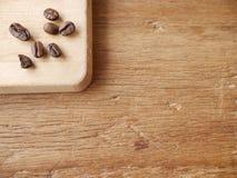 kaffebönor på skärbräda Fotografering för Bildbyråer