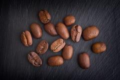 Kaffebönor på svart kritiserar bakgrund Arkivfoton