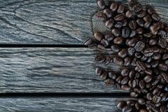 Kaffebönor på träbakgrund med korn och utrymme fotografering för bildbyråer