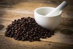 Kaffebönor på träbakgrunds- och vitmortel arkivbilder
