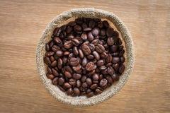 Kaffebönor på träbräde Arkivfoto