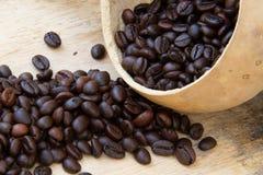 Kaffebönor på trägolv arkivfoton