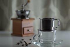 Kaffebönor på vitt trä med klart exponeringsglas och kaffekvarnen på bakgrund royaltyfri bild