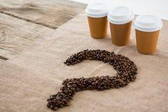 Kaffebönor som är ordnade i frågefläck, formar med disponibla kaffekoppar arkivfoto