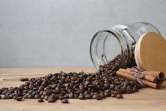 Kaffebönor som är utspillda från den Glass lilla kruset Fotografering för Bildbyråer