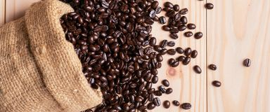 Kaffebönor som är utspillda från linnesäcken royaltyfri bild