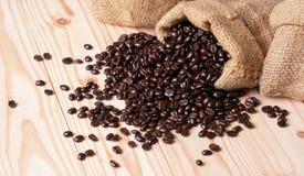 Kaffebönor som är utspillda från linnesäcken arkivfoto