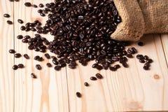 Kaffebönor som är utspillda från linnesäcken royaltyfria bilder