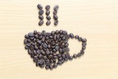 Kaffebönor som förläggas i form för kaffekopp Fotografering för Bildbyråer