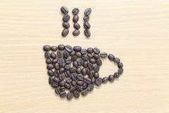 Kaffebönor som förläggas i form för kaffekopp Arkivbilder