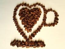 kaffebönor som grillas till att bilda en hjärtakopp arkivbild