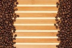 Kaffebönor som ligger på en matt bambu Arkivfoton