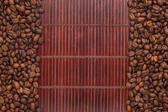Kaffebönor som ligger på en matt bambu Royaltyfri Fotografi