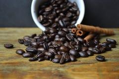 Kaffebönor som spiller ut ur den vita koppen med kanel Fotografering för Bildbyråer