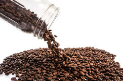 Kaffebönor som ut spiller glasflaskan Arkivbild