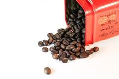 Kaffebönor spillde ut ur en isolerad krus - Royaltyfri Fotografi