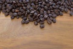 Kaffebönor spridda på den Wood tabellen royaltyfri bild
