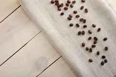 Kaffebönor spridda på en linnetorkduk Arkivbilder