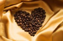 Kaffebönor spridda på tyg i form av hjärta Arkivfoto