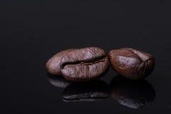 Kaffebönor svärtar den glansiga tabellen Royaltyfri Foto