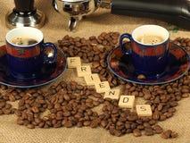 Kaffebönor, två utsmyckade koppar, fifflar och grupperar handtaget med bokstavsvännerna på en hessiansbackgroun Royaltyfri Fotografi