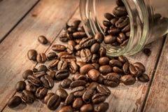Kaffebönor ut från exponeringsglas Arkivfoto