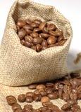 Kaffebönorna i påsen är på den vita bakgrunden Arkivfoto