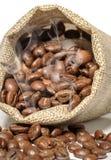 Kaffebönorna i påsen är på den vita bakgrunden Royaltyfria Foton