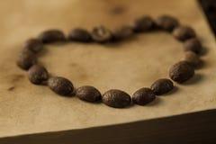 Kaffebönor i form av hjärta på gammal tappning öppnar boken Meny recept, åtlöje upp spelrum med lampa Arkivbild