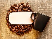 Kaffebönor med koppen och den tomma etiketten på säcken Royaltyfria Bilder