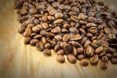 Kaffebönor på tappningträbräde Arkivbild