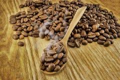 Kaffebönor på tappningträbräde Royaltyfria Bilder