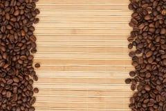 Kaffebönor som ligger på en matt bambu Royaltyfri Bild