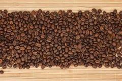 Kaffebönor som ligger på en matt bambu Royaltyfria Bilder