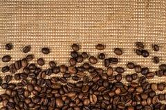 Kaffebönor spridda på burlap Arkivbilder