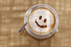 Kaffecappuccino med skum eller choklad som ler den välkomna lyckliga framsidan Royaltyfria Foton