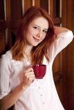 kaffedörrar som dricker flickan nära trä arkivbild