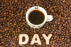 Kaffedagfoto Koppen med bryggat kaffe är på tabellen, som fyllde med grillade kaffebönor, bredvid ordavbrott Idé för globalt arkivfoton