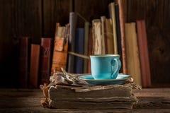 Kaffee auf Buch im blauen Porzellan in der Bibliothek stockfotografie