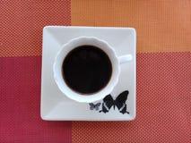 Kaffee auf eine Untertasse mit Schmetterlingsentwurf stockfoto
