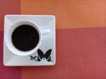 Kaffee auf eine Untertasse mit Schmetterlingsentwurf stockfotografie