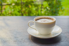 Kaffee auf einer hölzernen Tabelle mit einem natürlichen Hintergrund stockbilder