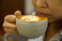 Kaffee auf Frauenhand in der Kaffeestube stockbild