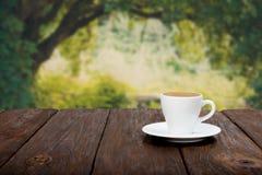 Kaffee auf Holztisch mit schönem forrest Hintergrund Stockfotografie
