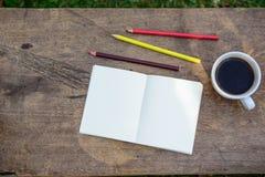 Kaffee, Bleistifte, Notizbücher werden auf dem Tisch heute morgen gesetzt Lizenzfreies Stockbild