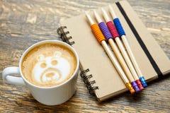 Kaffee, Bleistifte und Notizbuch Stockfotos