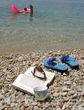 Kaffee, Buch, Sonnegläser auf Steinstrand Stockfotografie