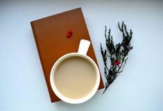 Kaffee, Buch und Niederlassung mit roten Beeren stockbilder
