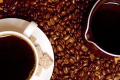 Kaffee, Caffeehersteller über Bohnenhintergrund Stockfotografie